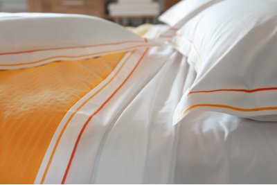 "Cotton sheets plain with orange double ""cordonetto"" embroidery.."