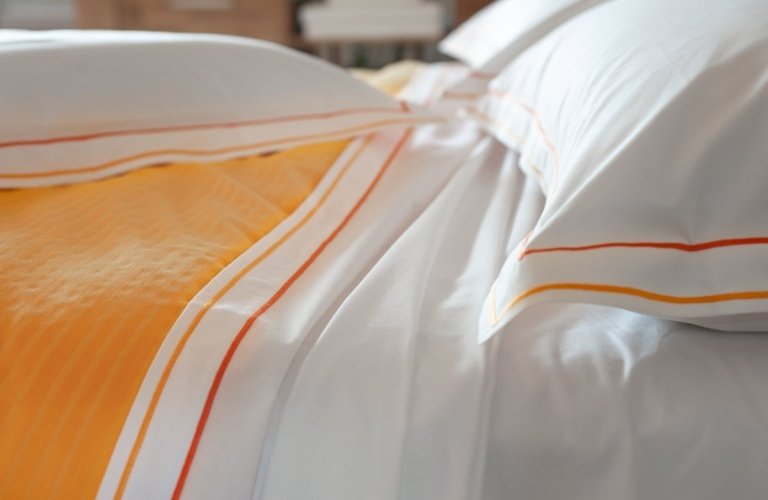 "Cotton sheets plain with orange double ""cordonetto"" embroidery."